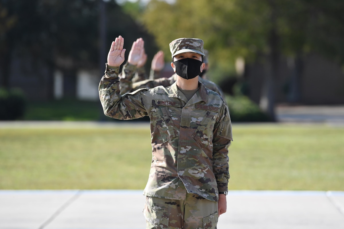 A line of airmen hold their right hands up as they recite an oath of enlistment.