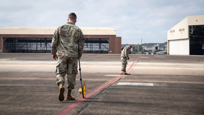 Master Sgt. Justin Consley 2nd Security Forces Squadron flight chief, and Master Sgt. Anton Hinrichsen, 2nd SFS technology and resources NCO in-charge, set up a cordon area for Global Thunder 21 at Barksdale Air Force Base, La., Oct. 20, 2020.