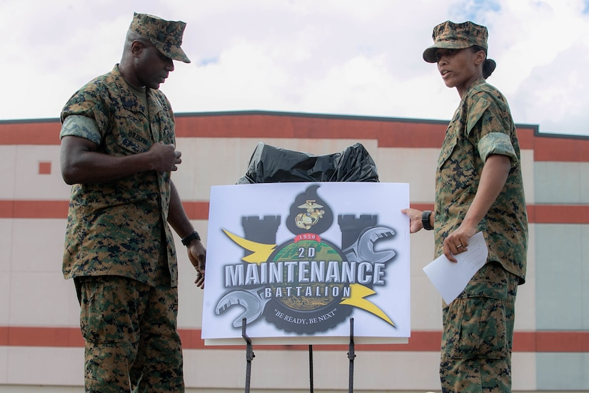 Marines stand next to a sign.