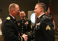 The Adjutant General of the Missouri National Guard, Brig. Gen. Levon Cumpton, recognizes Sgt. Joshua Roth during the National Guard Birthday Ball in December 2019, as the State Command Sergeant Major, Command Sgt. Maj. Kannon John looks on.