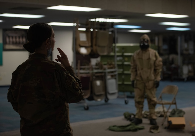 Airman instructs student in MOPP gear.
