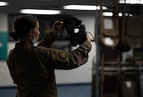 Airman holds protective gas mask.