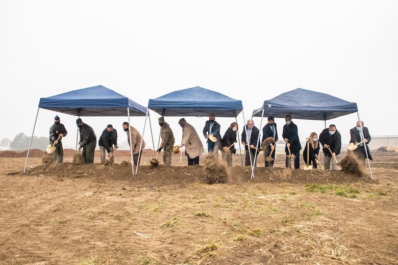Distinguished visitors shoveling dirt
