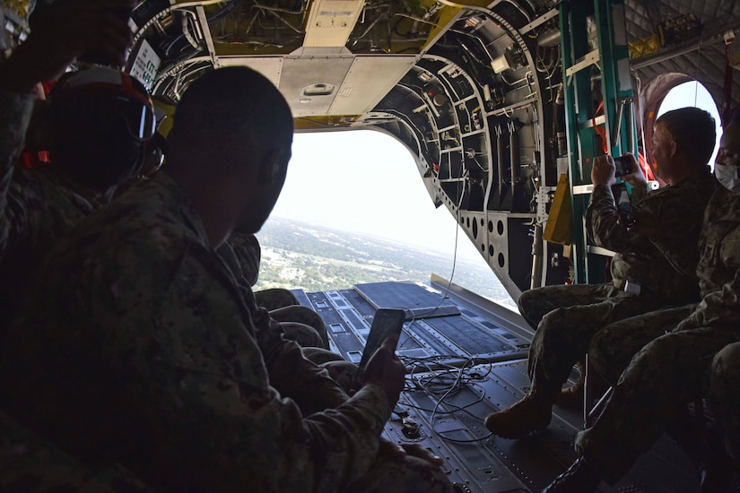 Service members sit in an aircraft.