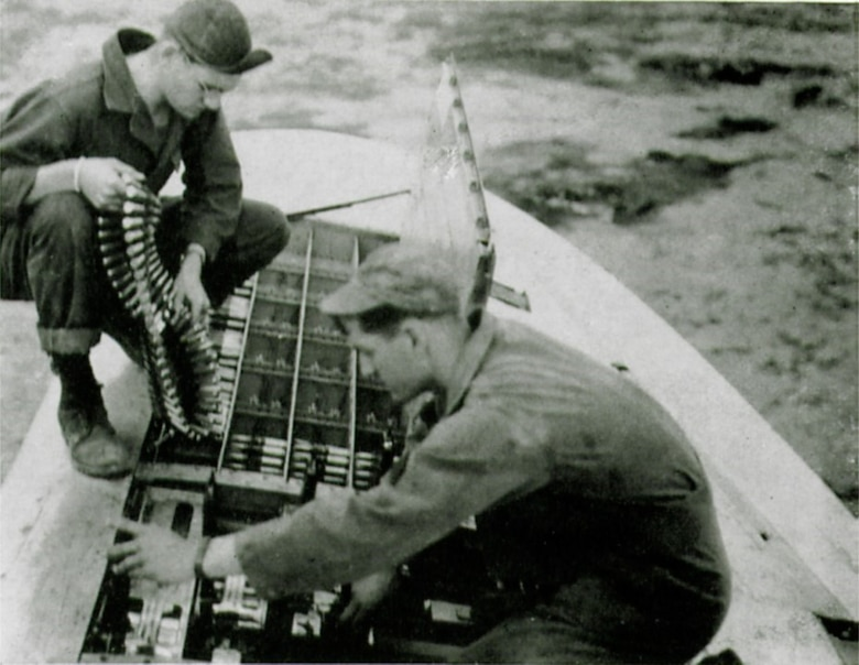 """Armorers Sgt. Douglas J. Wood and Sgt. Robert C. Dyson of the 406th Fighter Squadron """"loading them hot."""" (The Story of the 371st Fighter Group in the E.T.O.)"""