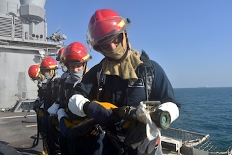 Seaman Alexis Ledesma inspects the firehose during a general quarters drill aboard the guided-missile cruiser USS Philippine Sea (CG 58) in the Arabian Gulf, Oct. 17.