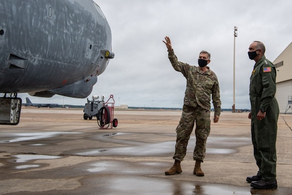 Two military leaders look at a B-52H Stratofortress at a military base.