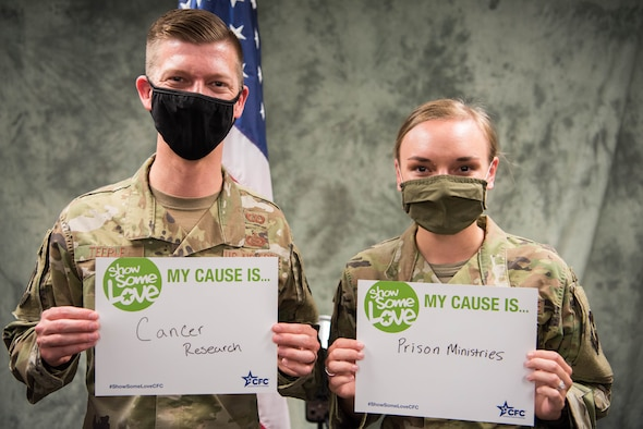 Two Airmen holding CFC cause signs