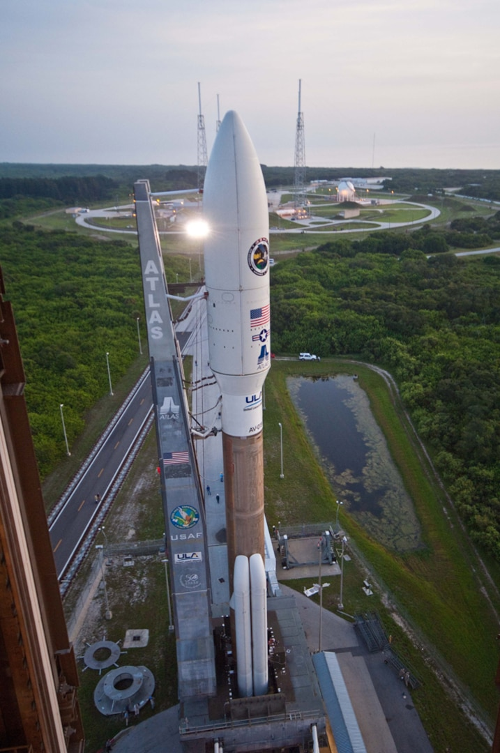 A rocket carrying a satellite payload prepares to launch from a launch pad
