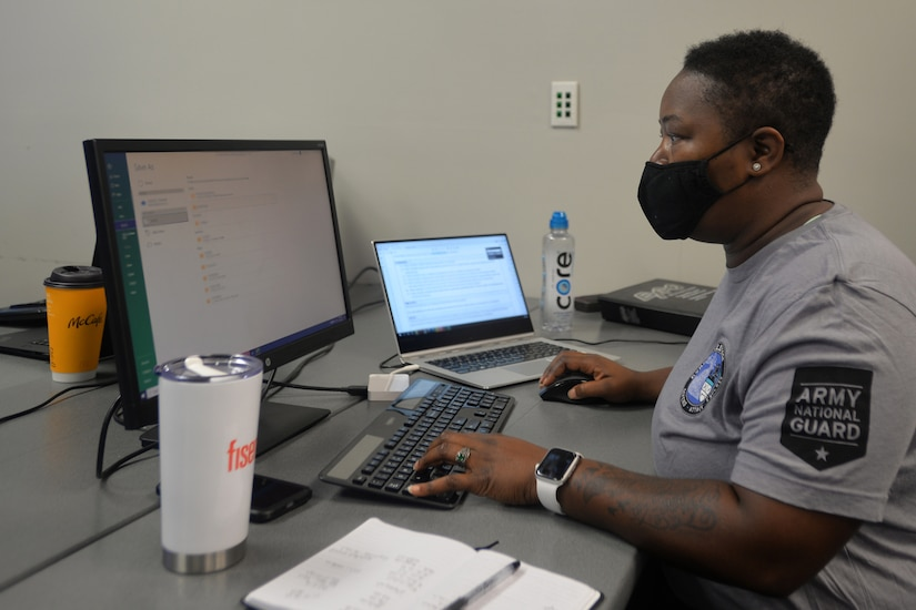 A woman wearing a mask works on a computer.
