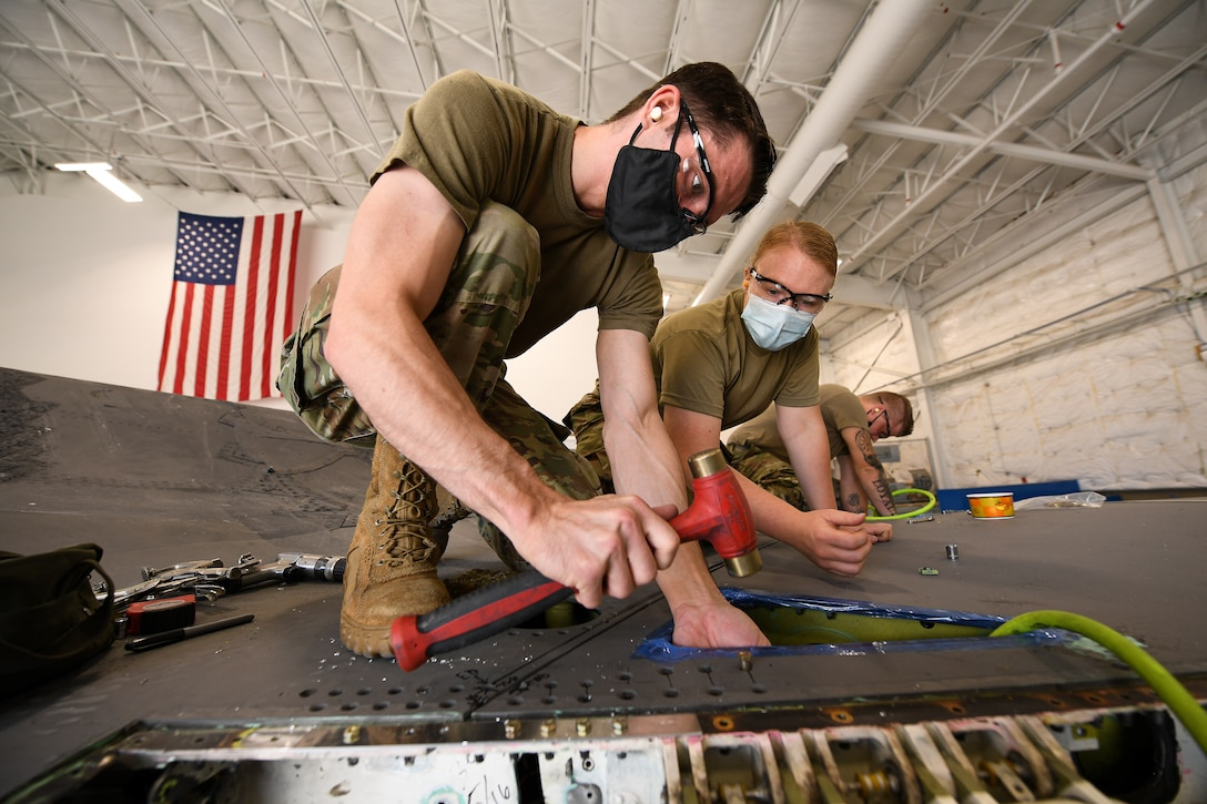 Tech. Sgt. Emil Wodicka, left, and Staff Sgt. Samantha Birnschein, 372nd Training Squadron Detachment 3, work a wing reattachment and repair on a repurposed F-35A Lightning II.