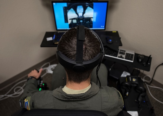 A photo of a pilot training on a VR simulator