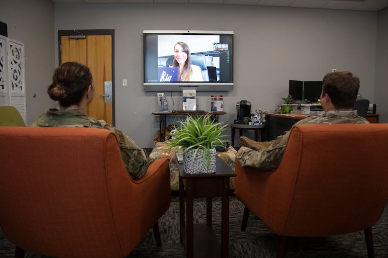 Photo of the back of two Airmen watching a TV