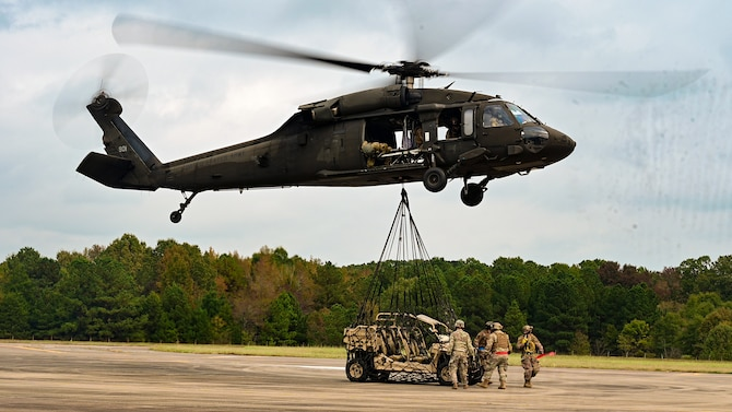 An off-road vehicle is attached to a helicopter for transport.