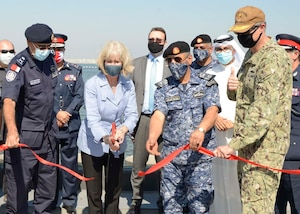 MANAMA, Bahrain (Oct. 21, 2020) Maggie Nardi, U.S. Embassy Chargé d'Affaires to the Kingdom of Bahrain, center, cuts a ribbon with Rear Adm. Curt Renshaw, deputy commander, U.S. Naval Forces Central Command, right, along with senior military and host nation leadership at a ceremony celebrating the installation of the coalition maritime forces waterfront security barrier at the Mina Salman Pier on board NSA Bahrain. The barrier is the first water-limited obstacle system security barrier system ever installed at an overseas naval installation, and the longest waterside security barrier in the U.S. Navy. NSA Bahrain enables the forward operations and responsiveness of U.S. and allied forces in support of Navy Region Europe, Africa, Central's mission to provide services to the fleet, warfighter and family. (U.S. Navy photo by Mass Communication Specialist 1st Class Justin Yarborough)