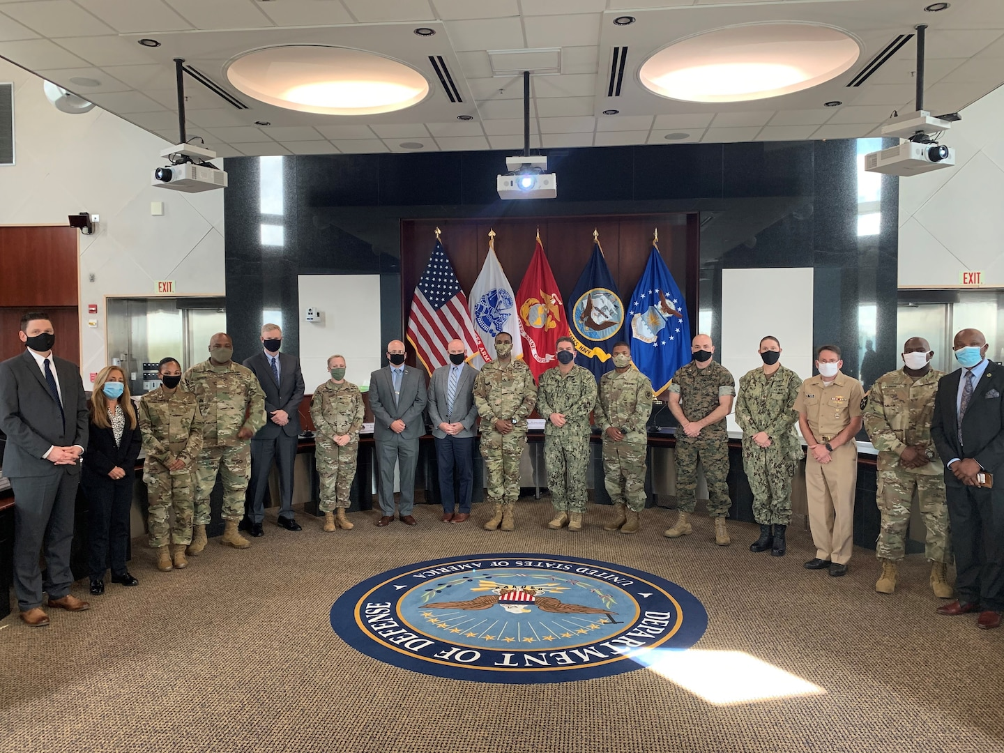 A group of military and civilian workers stand in a conference room.