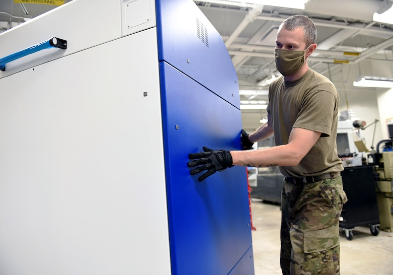 Staff Sgt. Joshua Turner, 149th Maintenance Squadron aircraft metals technician, moves a newly delivered printer into place at his unit's shop Aug. 12, 2020 at Joint Base San Antonio-Lackland, Texas. (Air National Guard photo by Mindy Bloem)