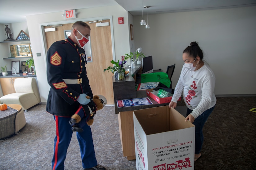 A Marine  prepares to drop a toy into a box.