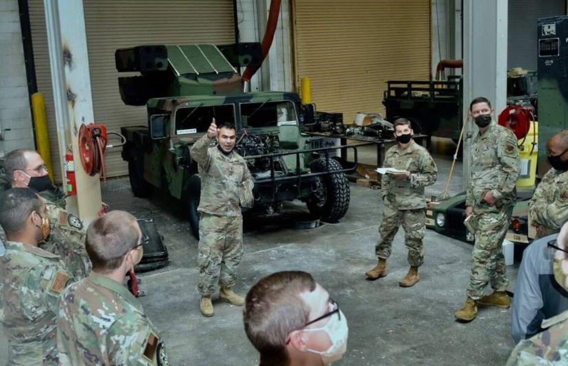 Airmen stand in garage with humvee