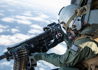 """Naval Air Crewman (Helicopter) 2nd Class Devin Haswell adjusts a .50-caliber machine gun in an MH-60S Sea Hawk helicopter, assigned to the """"Wildcards"""" of Helicopter Sea Combat Squadron (HSC) 23, currently embarked with the amphibious assault ship USS Makin Island (LHD 8)."""