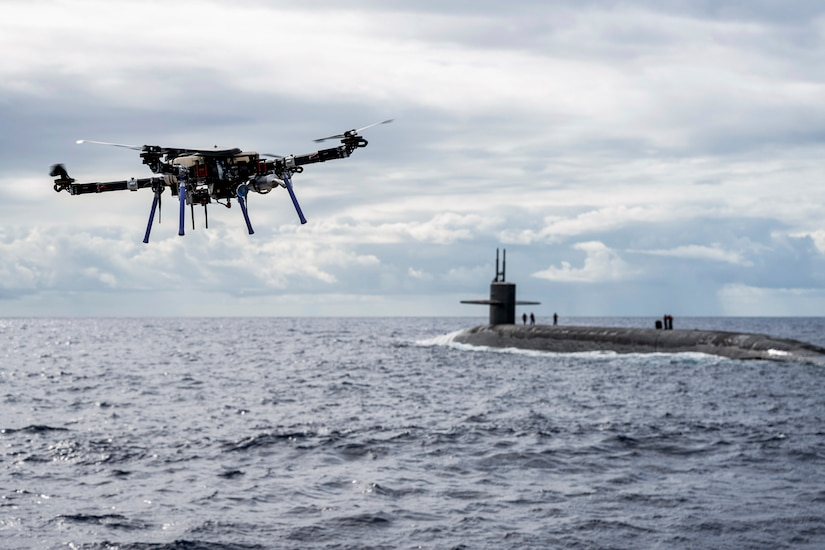 A drone flies over water near a submarine.