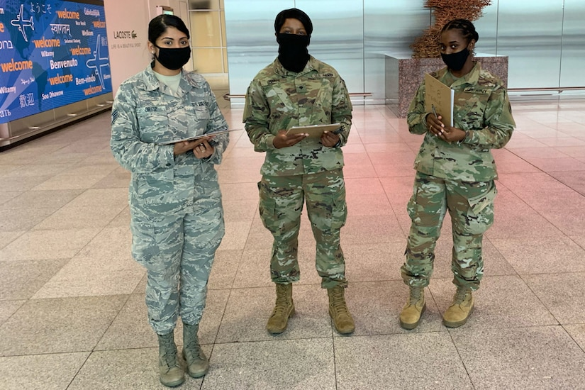 Three service members stand next to each other at an airport.