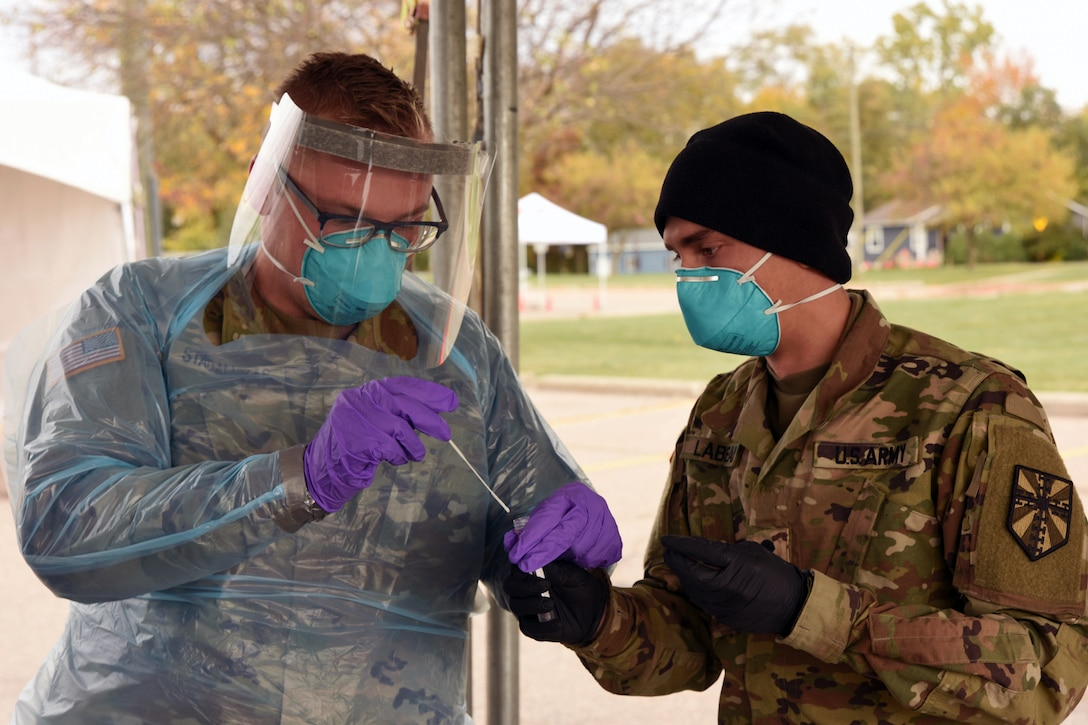 One service member dressed in personal protective equipment, puts a nasal swab into a test tube held by a service member wearing a face mask and gloves.
