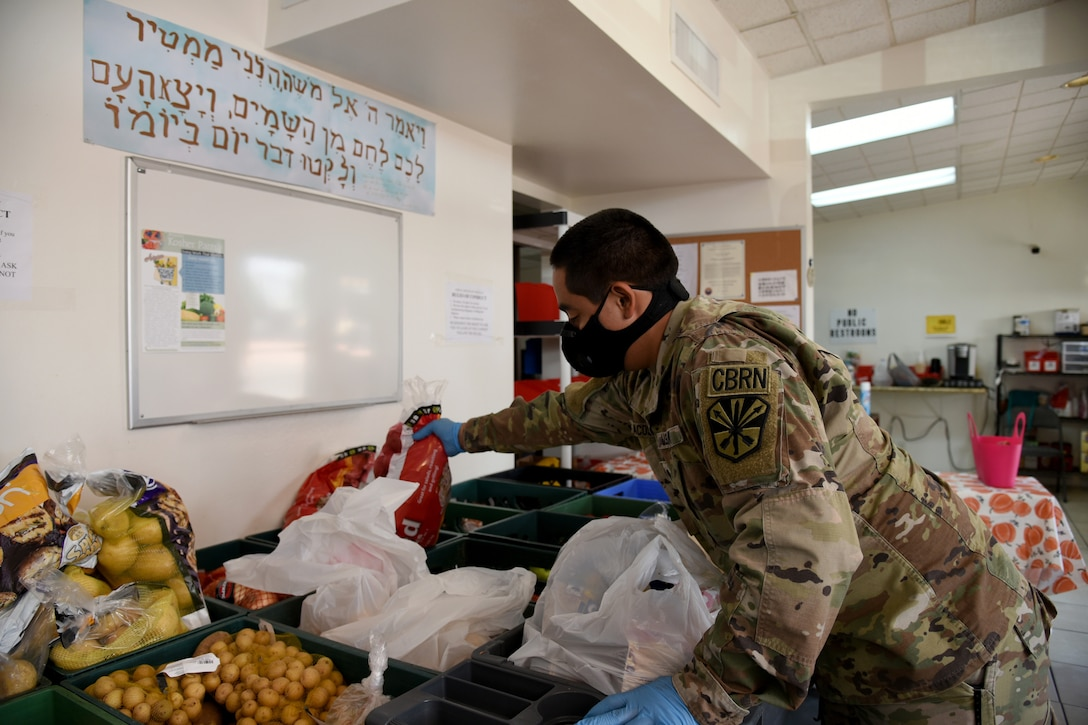 A guardsman wearing a face mask leans over a bin and picks up a bag of potatoes.