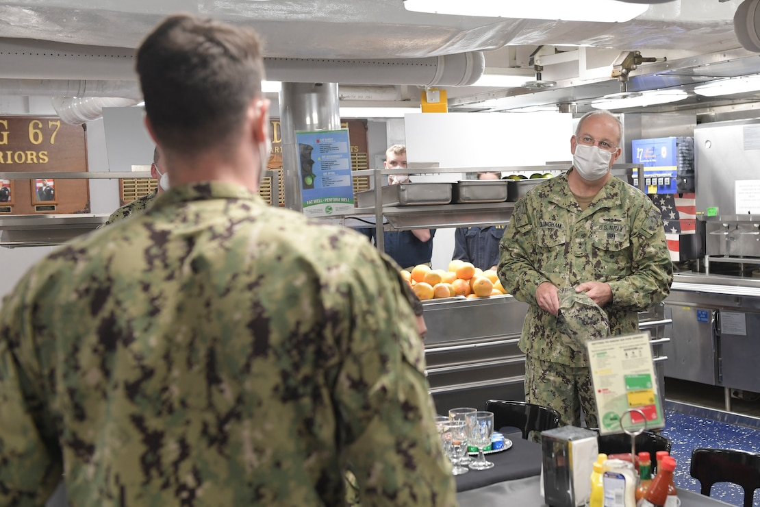 Rear Adm. Bruce Gillingham, right, the surgeon general of the Navy, speaks with Sailors assigned to USS Cole (DDG 67) during a visit aboard the ship.