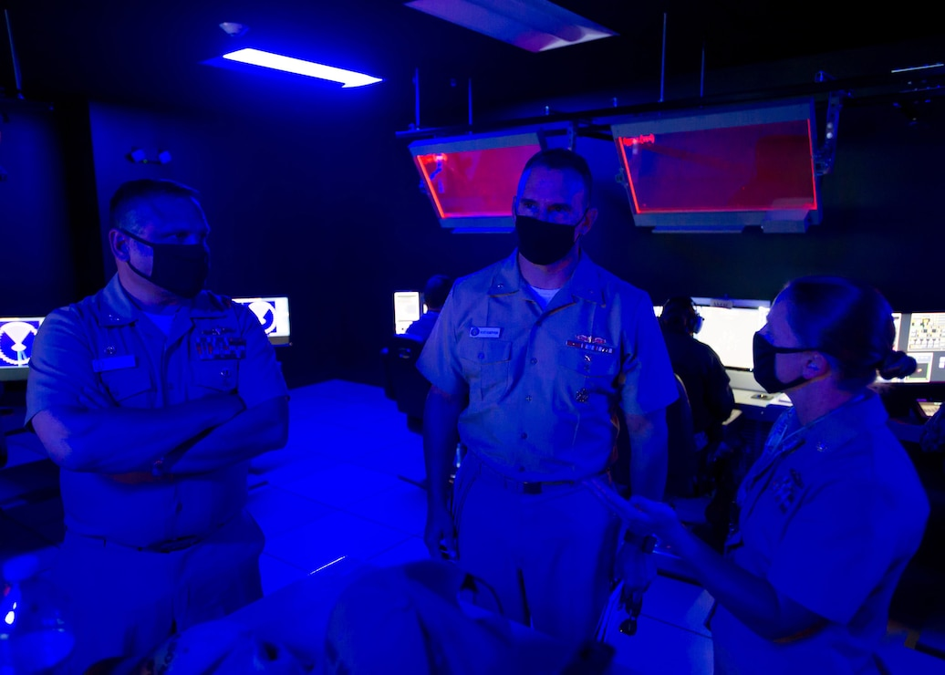 Rear Adm. Scott Robertson, commander, Naval Surface and Mine Warfighting Development Center (SMWDC), tours inside the Reconfigurable Combat Information Center Trainer (RCT) during his visit to the Center for Surface Combat Systems (CSCS) and CSCS