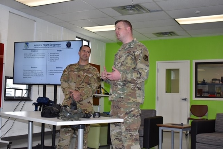 Photo shows two Airmen standing while addressing a room.