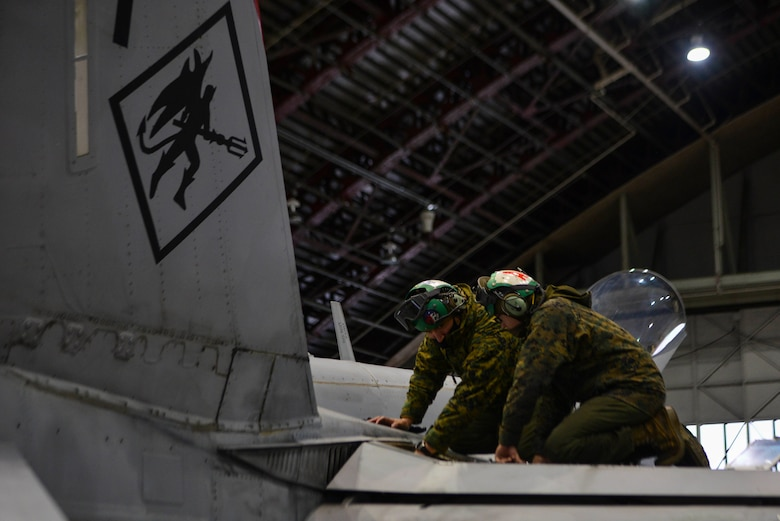 U.S. Marine Corps Gunnery Sgt. Jason C. Alvarez, Sr. (left), the Marine Fighter Attack Squadron (VMFA) 232 airframes division chief, and Pfc. Michael A. Flores, a VMFA-232 airframes mechanic, install a trailing edge flap servo on an F/A-18 Hornet during RED FLAG-Alaska (RF-A) 21-1 at Eielson Air Force Base, Alaska, Oct. 21, 2020.