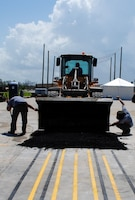 The Air Force Civil Engineer Center Lab research team place a hot-mix asphalt cap on top of the K-Fill CLSM backfill during field evaluations.