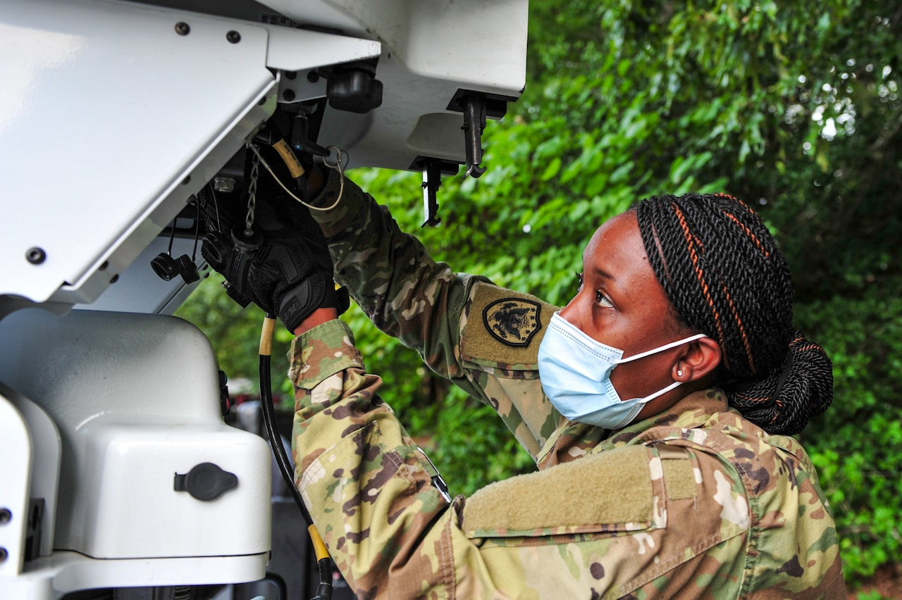 A woman works on satellite equipment.