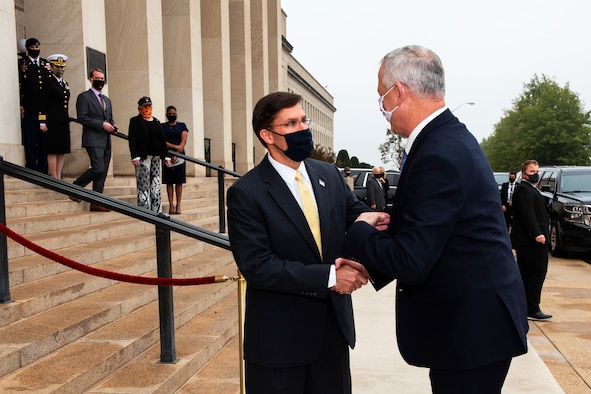 Two men dressed in suits and wearing face masks greet one another with a handshake outside a large building.