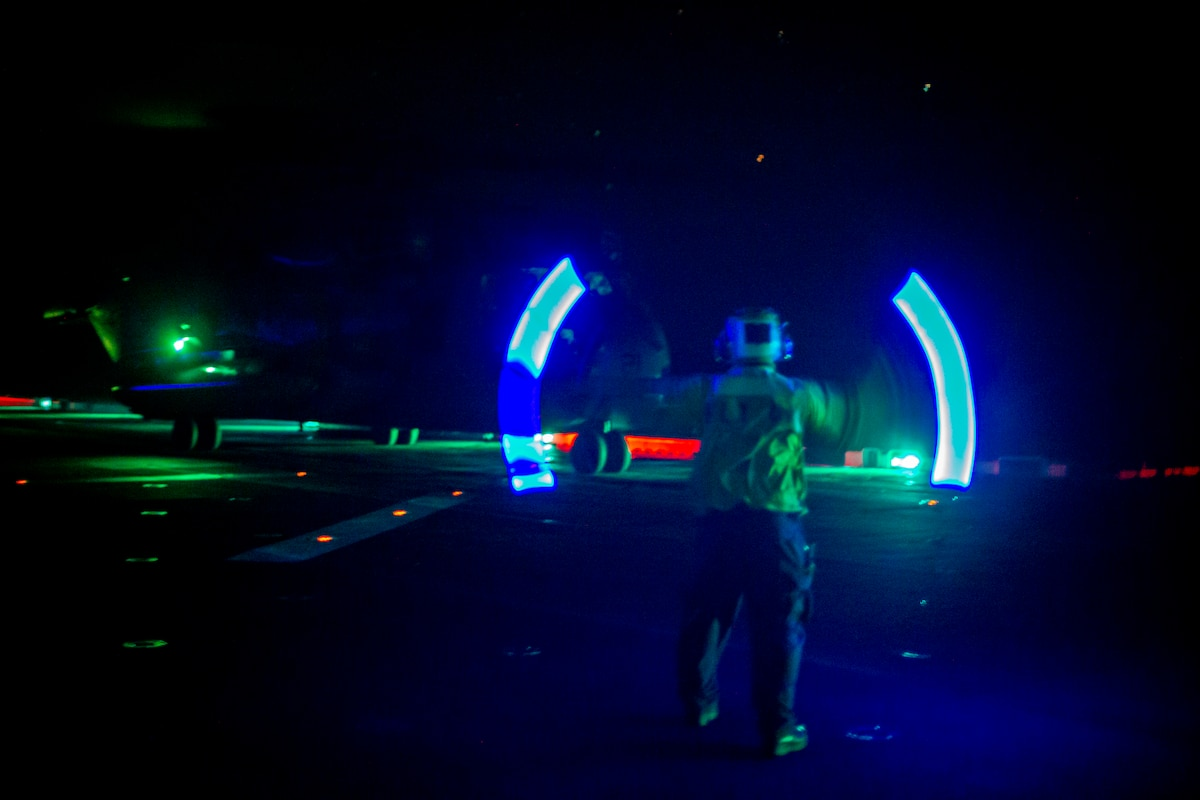 A sailor directs an aircraft illuminated by green and blue light.