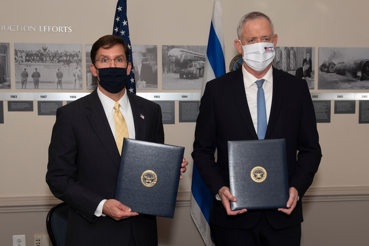 Two men dressed in suits and wearing face masks stand next to one another; each holds a binder with a seal in the middle.