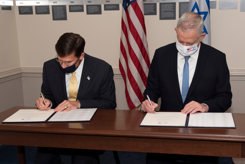 Two men dressed in suits and wearing face masks sit next to one another; each is signing a document.