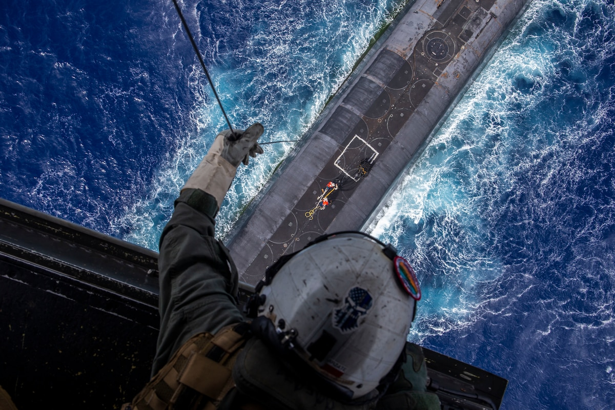A Marine, shown from above, lowers a line from an open aircraft to a submarine in water.