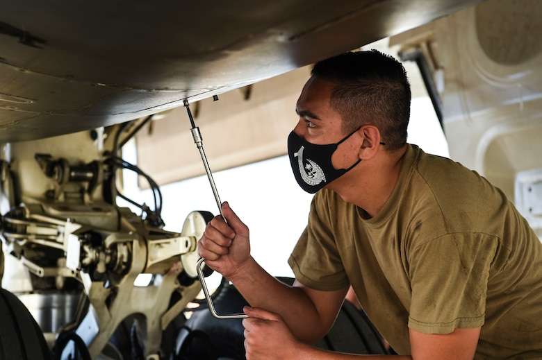 Senior Airman Zach Cruz, 9th Expeditionary Bomb Squadron crew chief, closes a panel after inspecting a B-1B Lancer auxiliary power unit during a Bomber Task Force deployment at Andersen Air Force Base, Guam, Oct. 20, 2020.