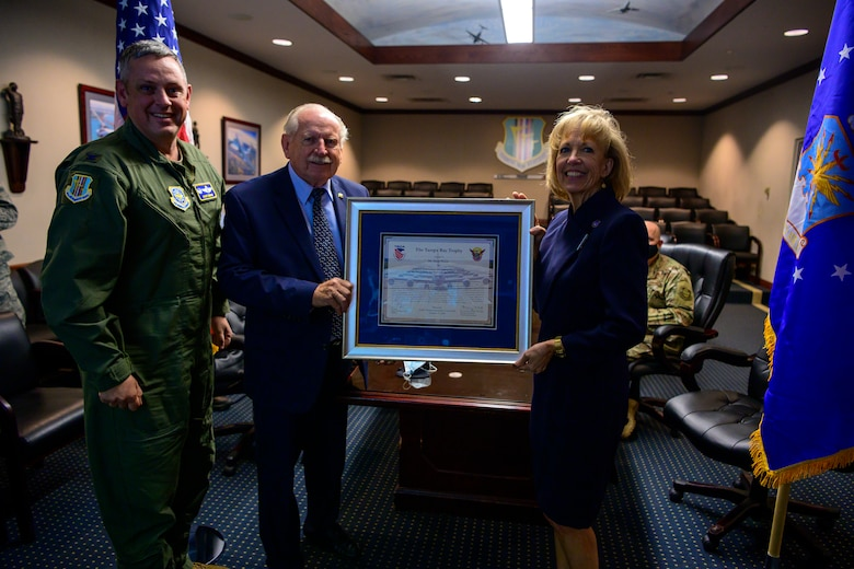 A woman in a navy dress holds a large framed certificate being presented to her by two men.