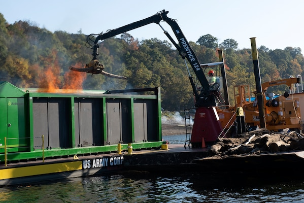 Lead Operator Jesse Neal operates the grapple crane on the PRIDE of the Cumberland, placing debris into an air curtain burner on a new floating barge Oct. 21, 2020 in Lake Cumberland near Waitsboro Recreation Area in Somerset, Kentucky. (USACE Photo by Lee Roberts)