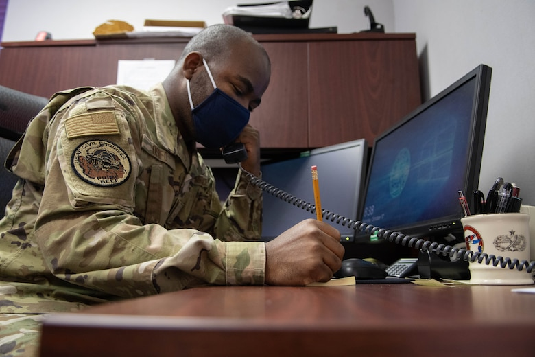 An Airman sits a desk, speaking on the phone and taking notes.