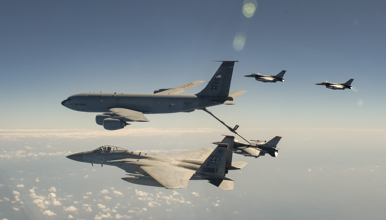 A tanker aircraft refuels a jet midair as three other jets fly nearby.