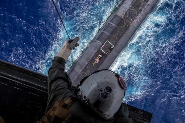"""Marine attached to """"Lucky Red Lions"""" of Marine Medium Tiltrotor Squadron 363 lowers payload from MV-22B Osprey to USS Henry M. Jackson in vicinity of Hawaiian Islands, Pacific Ocean, October 21, 2020 (U.S. Marine Corps/Matthew Kirk)"""