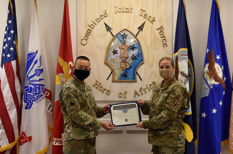 U.S. Army Maj. Gen. Lapthe C. Flora stands to the left presenting a promotion certificate to  U.S. Air Force Tech. Sgt. Dana Cable standing on the right