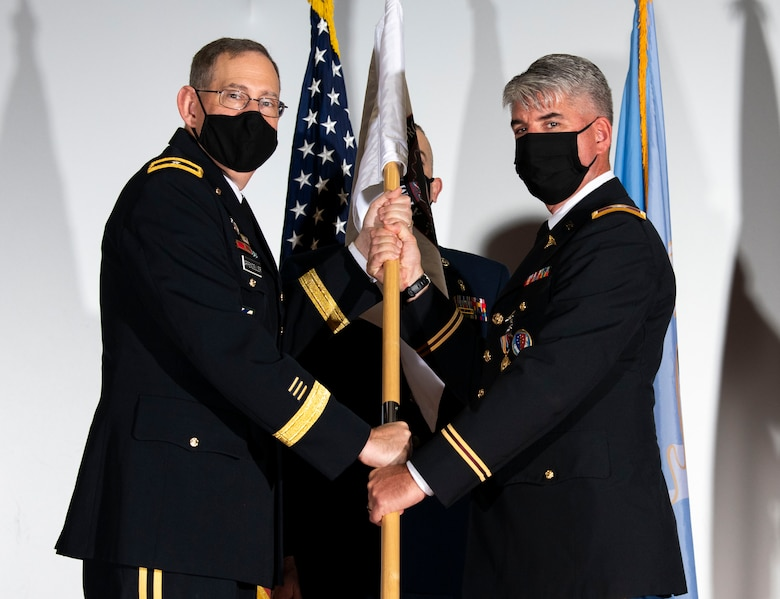 U.S. Army Brig. Gen. George Appenzeller (left), Defense Health Agency assistant director, presents the Armed Forces Medical Examiner System guidon to U.S. Army Col. Louis Finelli, outgoing AFMES director, during a change of directorship ceremony at Dover Air Force Base, Delaware, Oct. 21, 2020. AFMES provides the Department of Defense and other federal agencies comprehensive forensic investigative services, to include forensic pathology, DNA forensics, forensic toxicology and medical mortality surveillance. (U.S. Air Force photo by Senior Airman Christopher Quail)