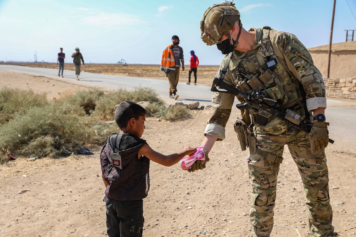A soldier hands candy to a child in desert-like area as others walk nearby.