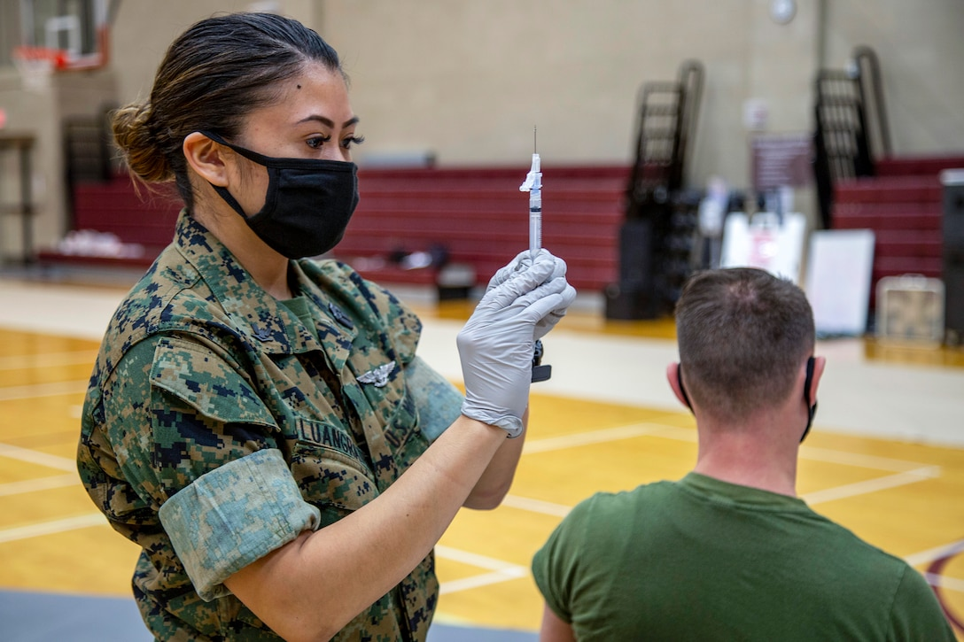 A Marine wearing a mask stands and holds up a syringe as a Marine sits in a chair beside her.