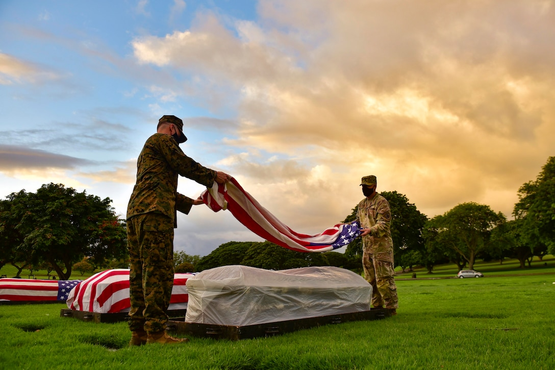 A Marine and a soldier place an American flag on a casket.